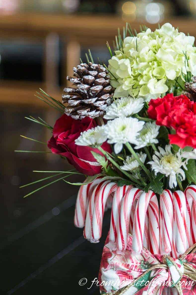 Add evergreen sprigs and pine cone picks | Add some holiday spirit to your Christmas table decor with this red and white DIY candy cane Christmas centerpiece! | DIY Quick and Easy Candy Cane Christmas Centerpiece