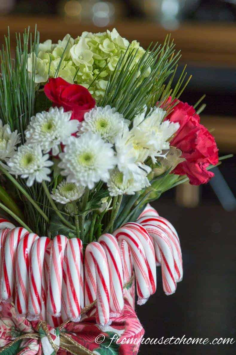 Add the flowers and fill in with the greens | Add some holiday spirit to your Christmas table decor with this red and white DIY candy cane Christmas centerpiece! | DIY Quick and Easy Candy Cane Christmas Centerpiece