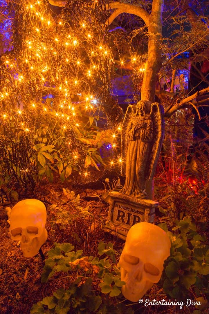 Halloween graveyard with orange string lights with skulls and a Halloween gravestone