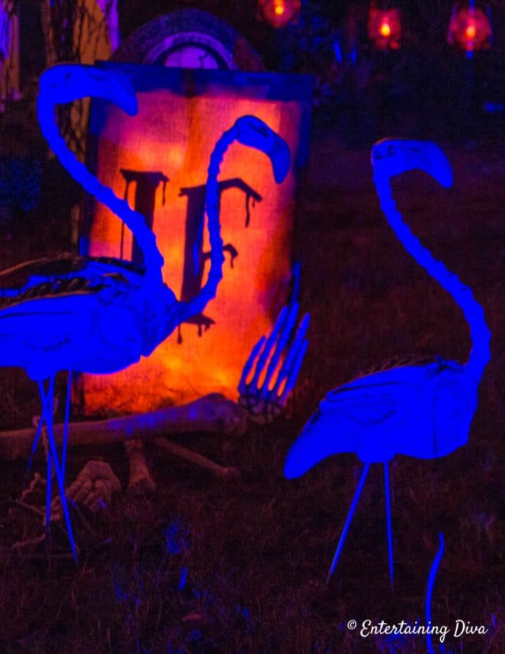Skeleton flamingos in a Halloween graveyard