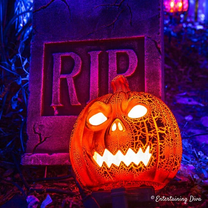 Halloween pumpkin in front of gravestone
