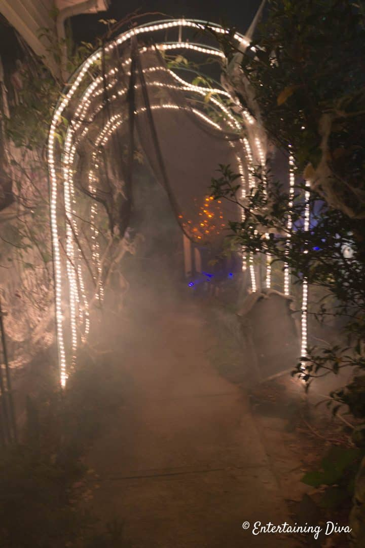 White lights on an arbor reflect off of Halloween graveyard fog