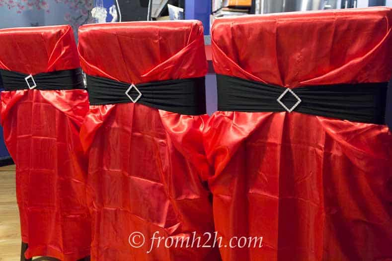 Red chair cover with black sash and a little bling - Fallen Angels and Devils Party | www.fromhousetohome.com/entertainingdiva
