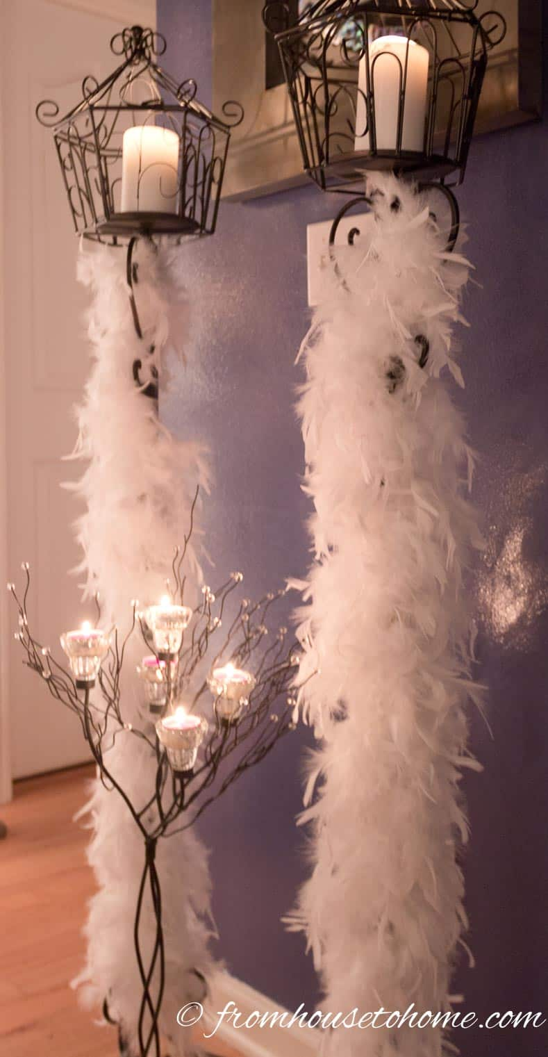 White feather boas wrapped around candle sticks look like snow while adding texture | Winter Wonderland Party Ideas