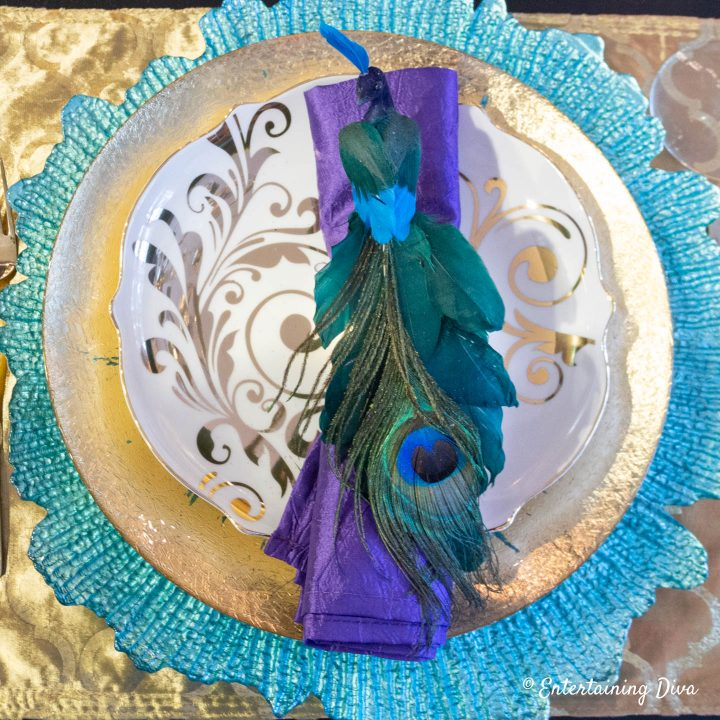 Peacock place setting with purple napkin, turquoise charger and gold plate