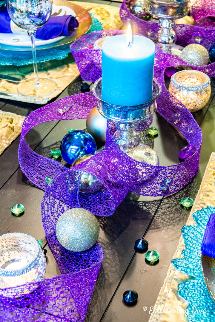 Teal candle with purple wired ribbon and gold Christmas ornaments in a peacock-inspired tablescape centerpiece