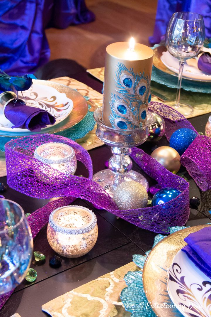 Gold and teal peacock pillar candle with purple wired ribbon as a Mardi Gras centerpiece