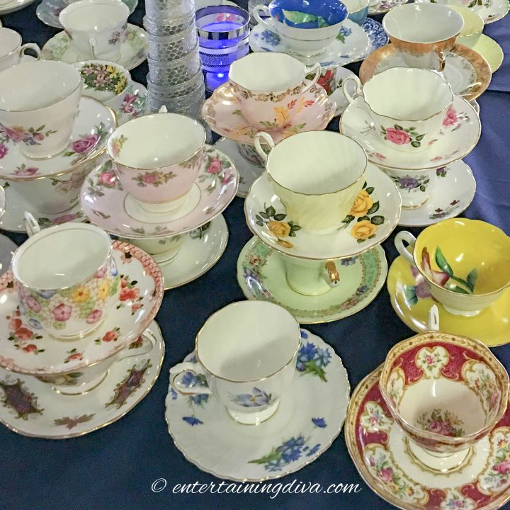 A table full of mixed and matched tea cups and saucers