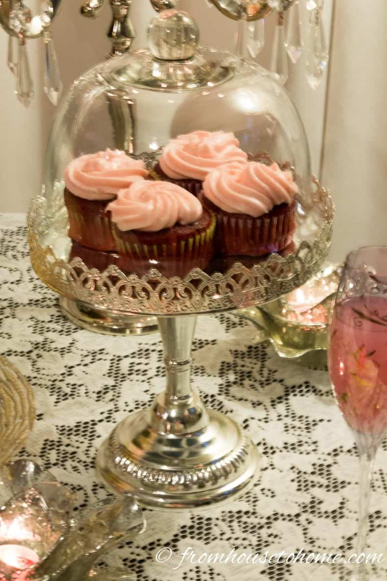 Red velvet cupcakes with pink icing on a silver cake tray