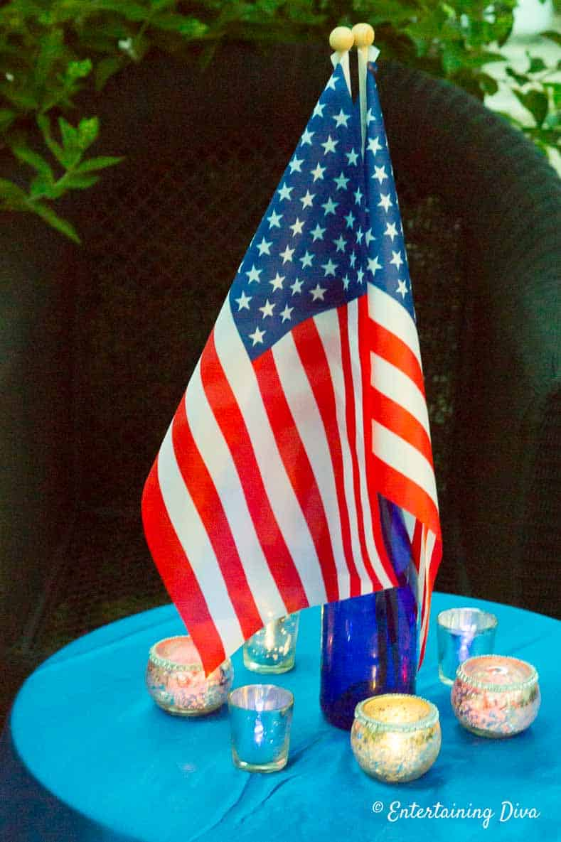 Using blue wine bottles as a flag stand to create a patriotic centerpiece