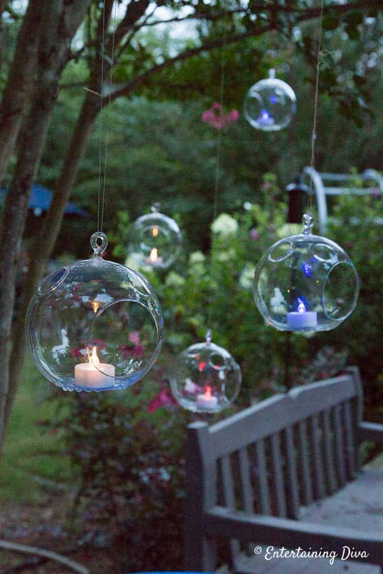 Red, white and blue flameless tealights hanging from tree are an Easy 4th of July Outdoor Decorating Idea