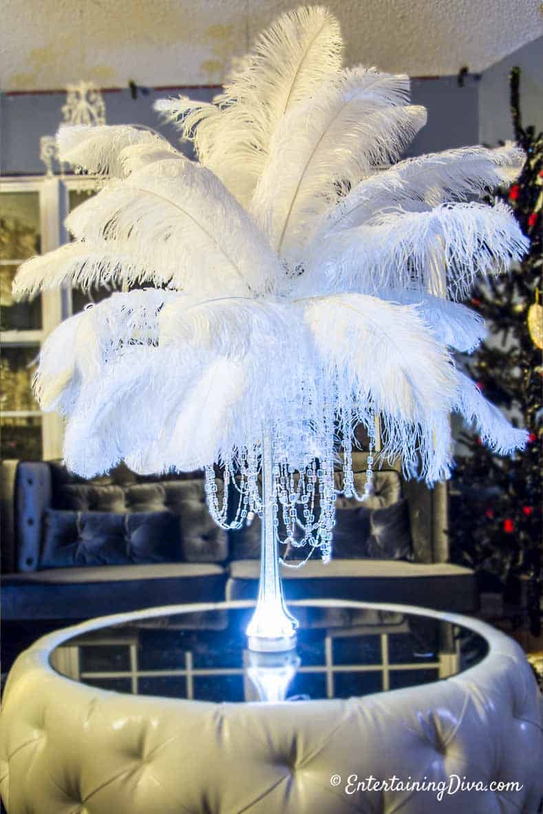 White ostrich feathers hung with crystals in an eiffel tower vase as a Great Gatsby party centerpiece