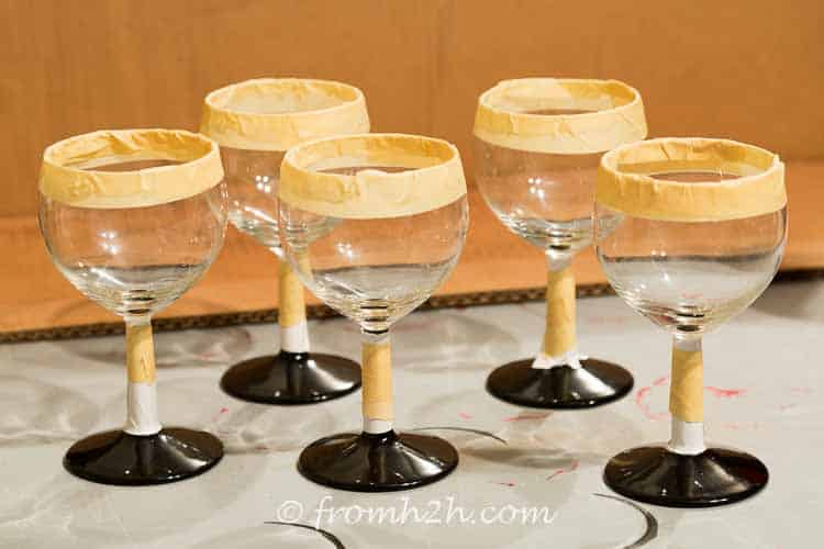 Tape the top of the glass and cover the stem | DIY Santa Wine Glasses