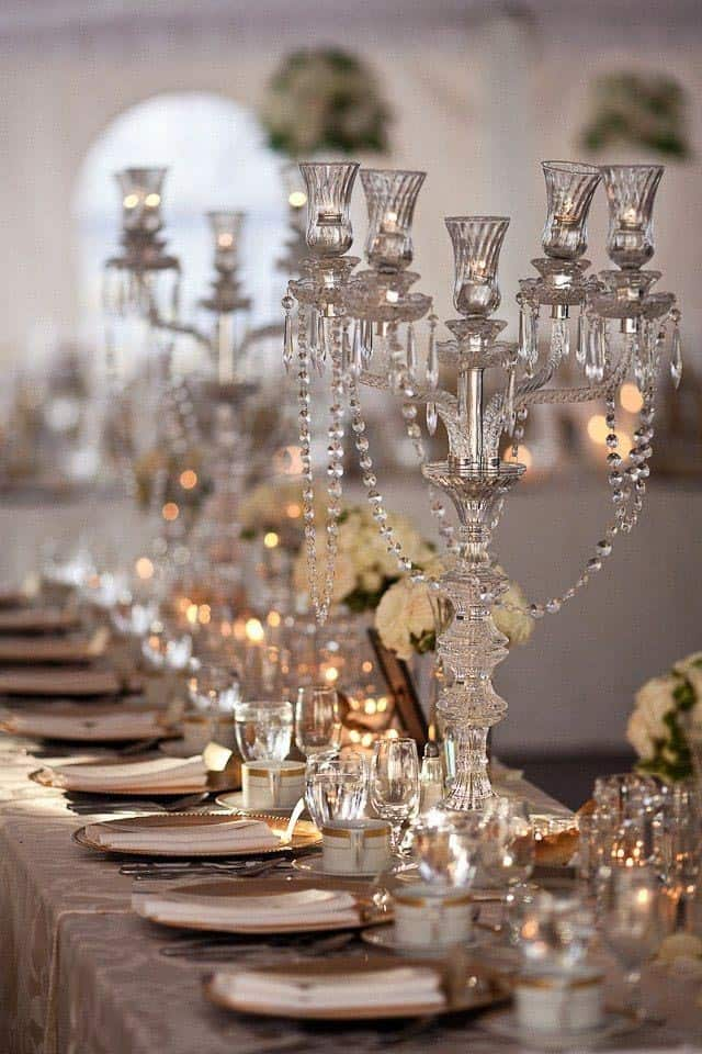 Gatsby party centerpiece with crystal candelabras and white roses in vases from blog.hotchocolates.co.uk
