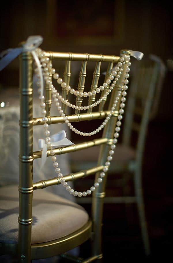 Gold bamboo chairs with white string of pearls on the back from lovemydress.net