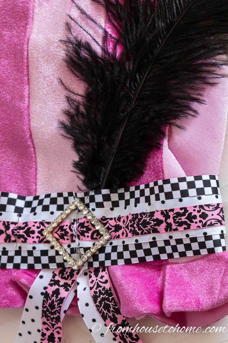 Add feathers behind the ribbon using the back of the sash pin to hold them