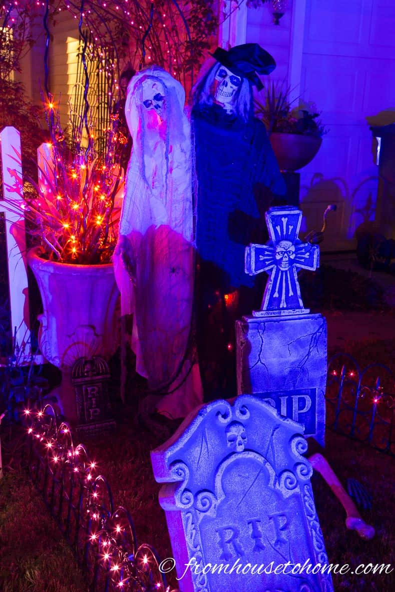 Halloween ghosts in a graveyard lit with a blue spotlight