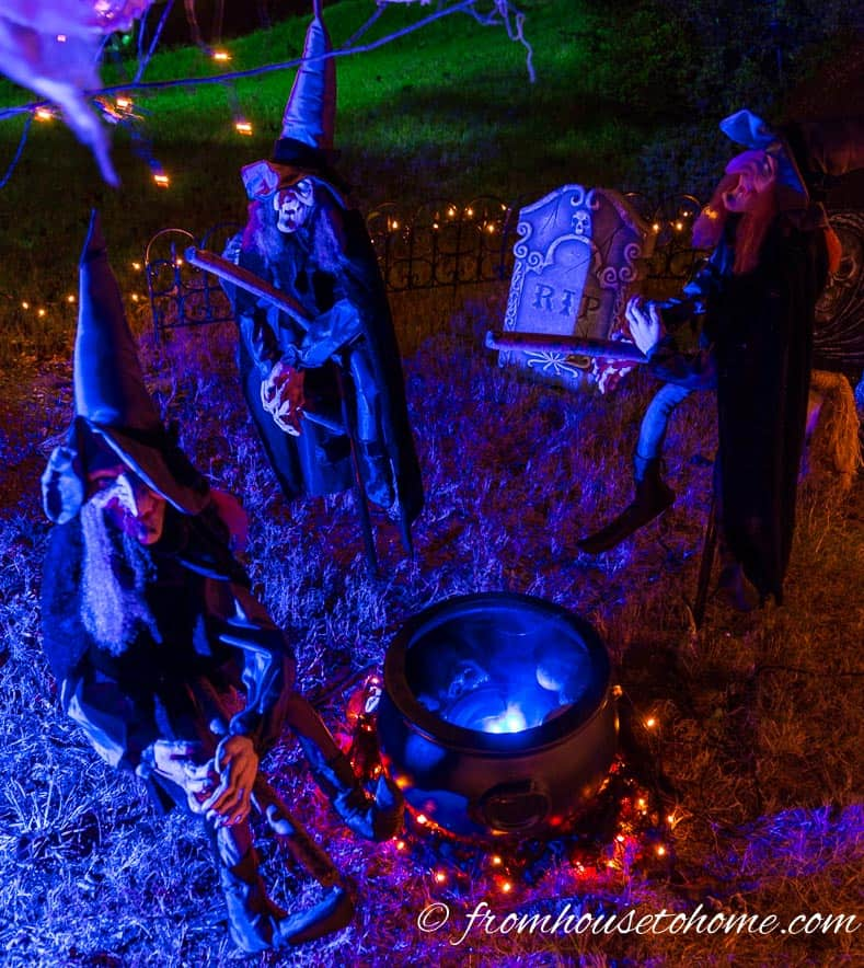 Halloween yard display with witches and boiling cauldron