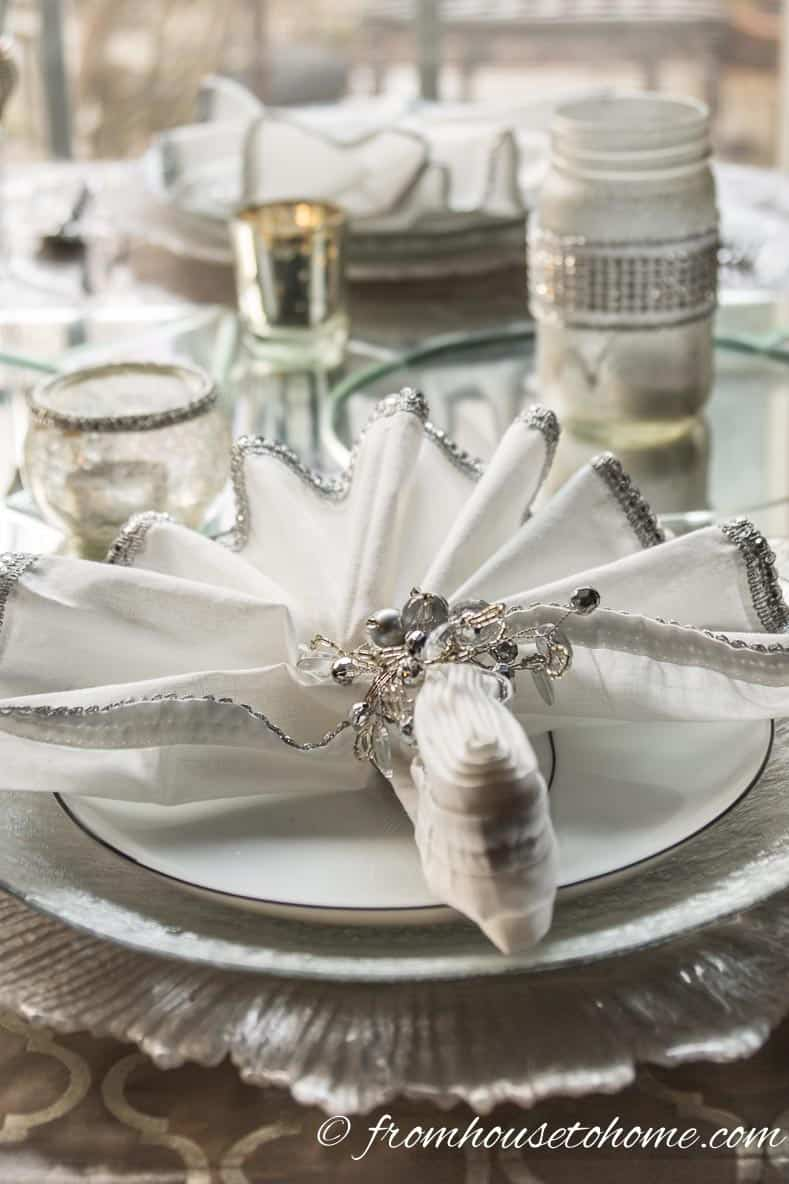 White napkins with silver edging and silver snowflake napkin rings | Silver and White Winter Table Setting