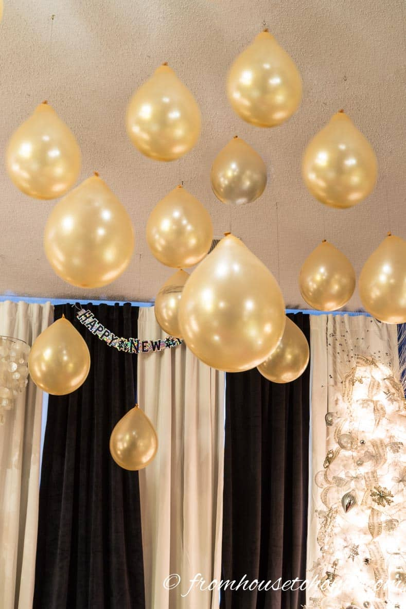 Gold balloons hung from the ceiling are an easy last minute New Year's Eve party decor idea