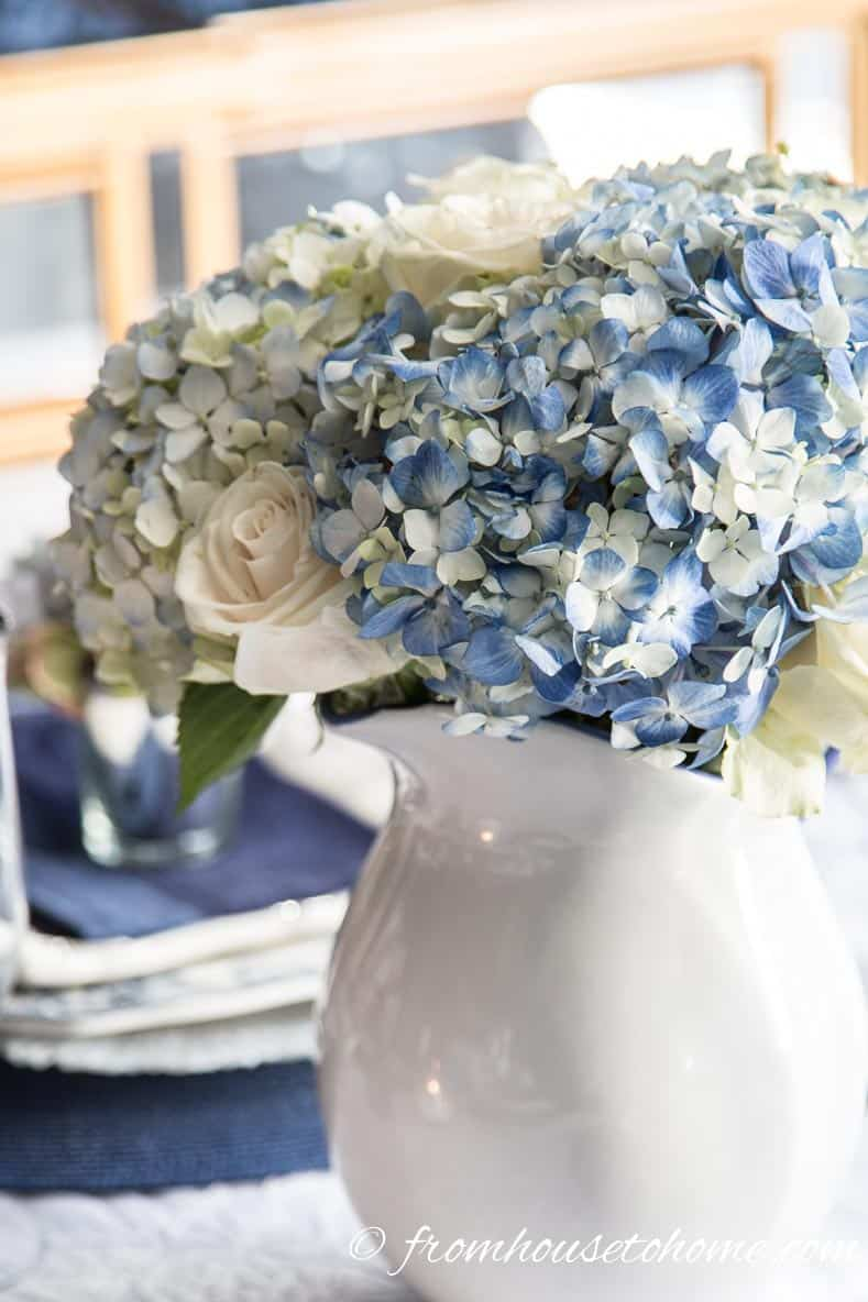 Hydrangea-inspired Blue and White Tablescape | If you're looking for Easter dinner or spring table ideas, this blue and white table setting has a hydrangea centerpiece that is perfect for the occasion. The blue and white place setting is really pretty, too.