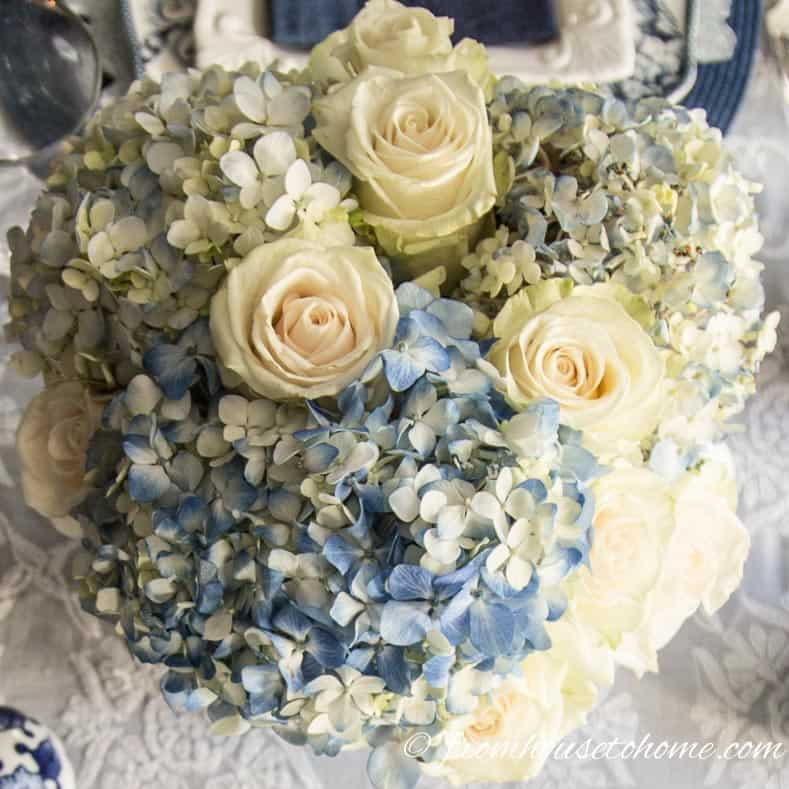 White roses look good with the hydrangeas | Hydrangea-inspired Blue and White Tablescape | If you're looking for Easter dinner or spring table ideas, this blue and white table setting has a hydrangea centerpiece that is perfect for the occasion. The blue and white place setting is really pretty, too.