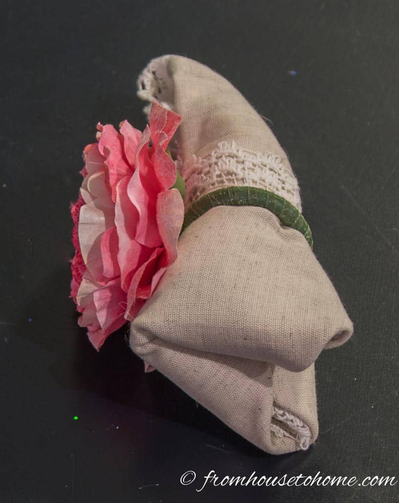 Slip a napkin ring over the top end of the folded napkin
