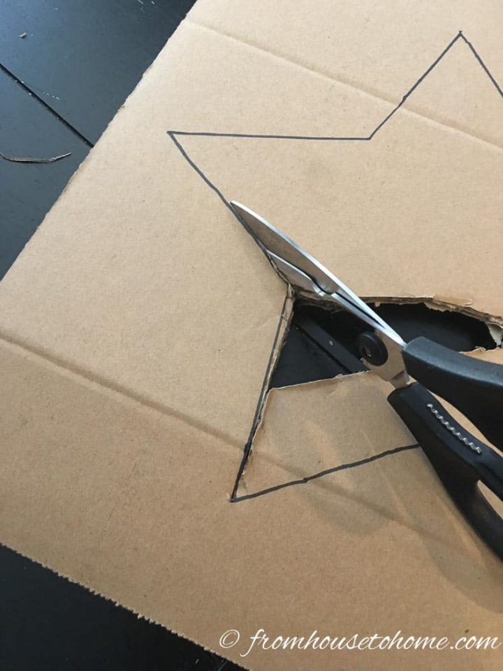 Scissors cutting out a star from a piece of cardboard