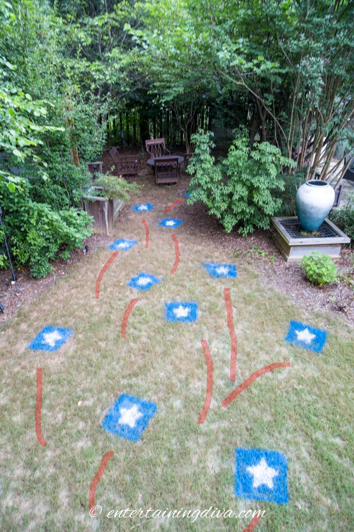 The backyard with red, white and blue stars painted on the grass as 4th of July party decor