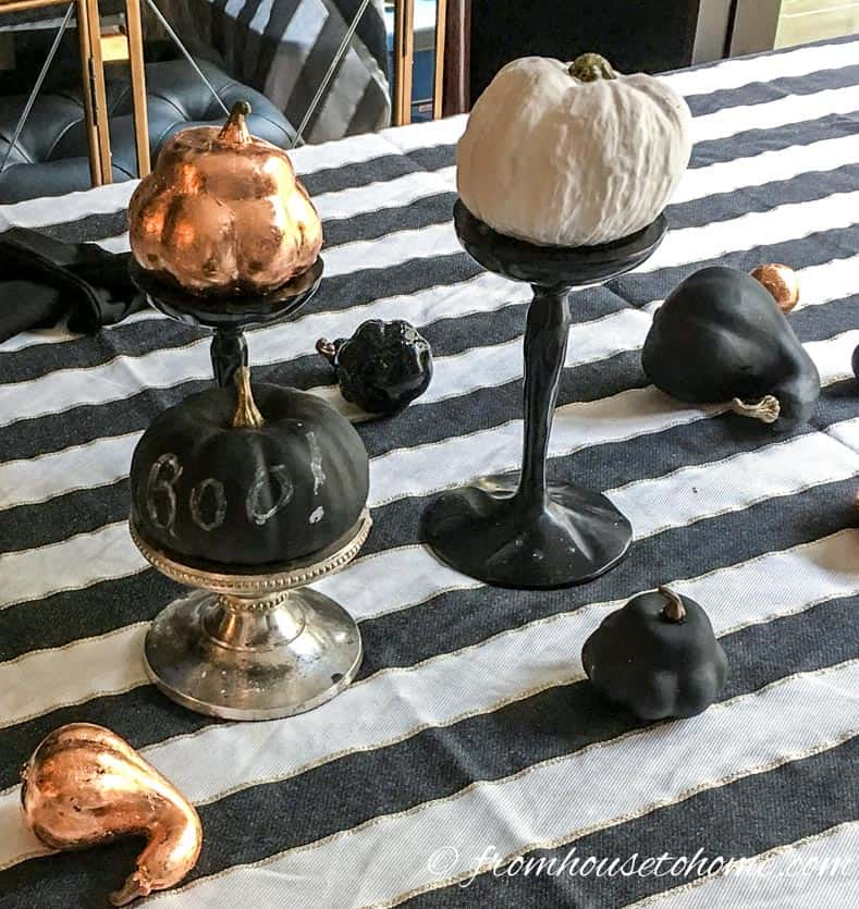 Black, white and copper mini pumpkins on a black and white striped table cloth