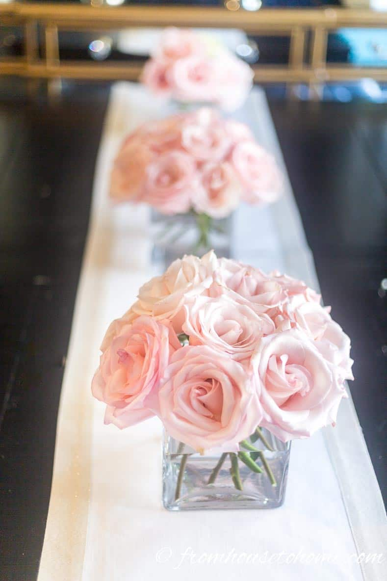 Pink roses in square vases on a table runner