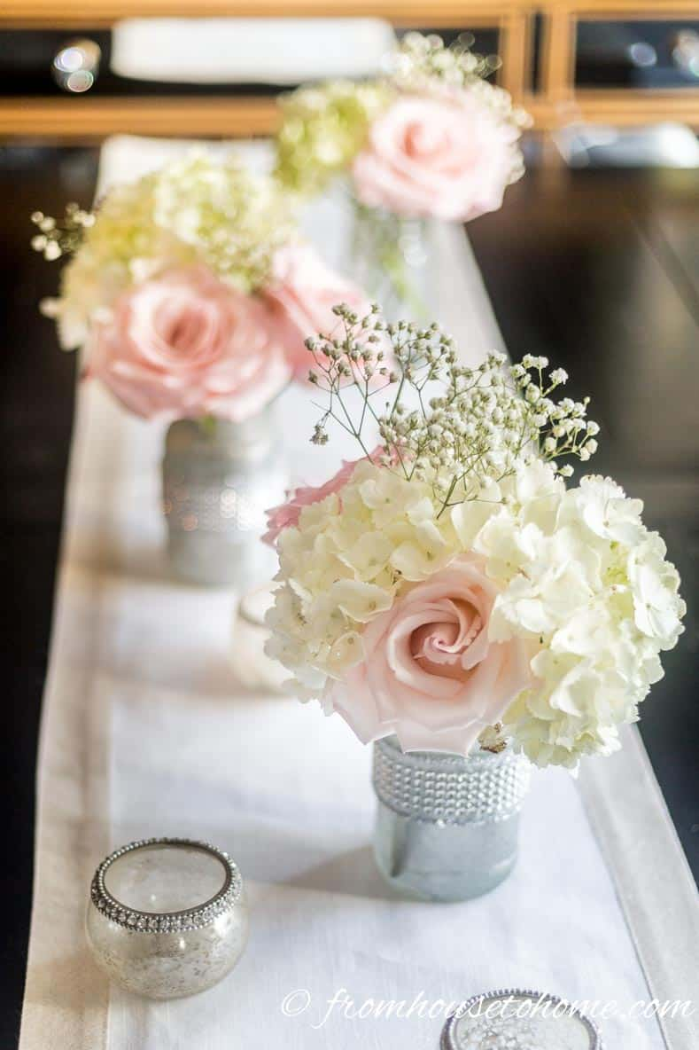 Elegant pink floral centerpiece made from silver-painted mason jars holding white hydrangeas, pink roses and white baby's breath