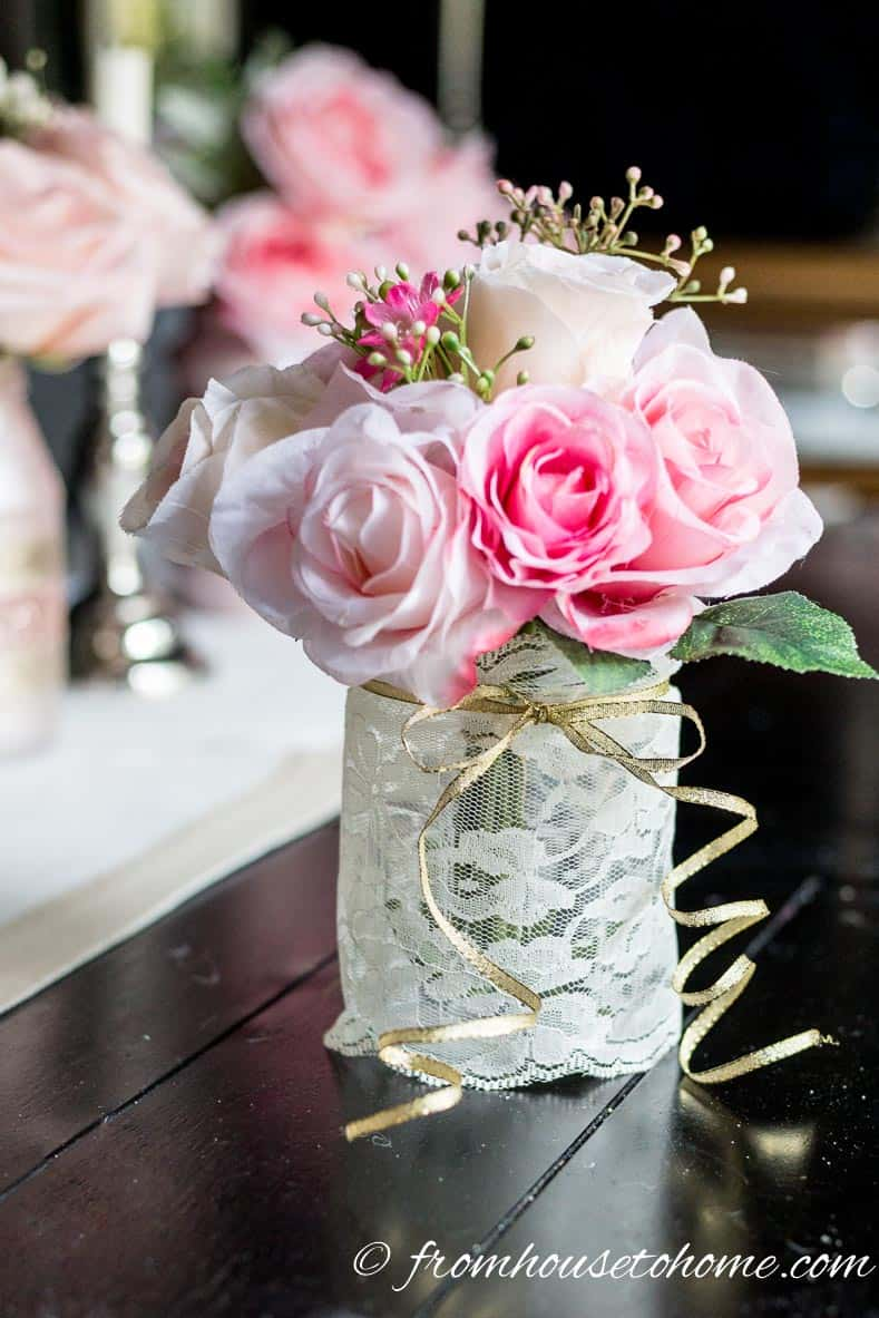 DIY pink flower centerpiece made with a mason jar wrapped in white lace and a gold ribbon