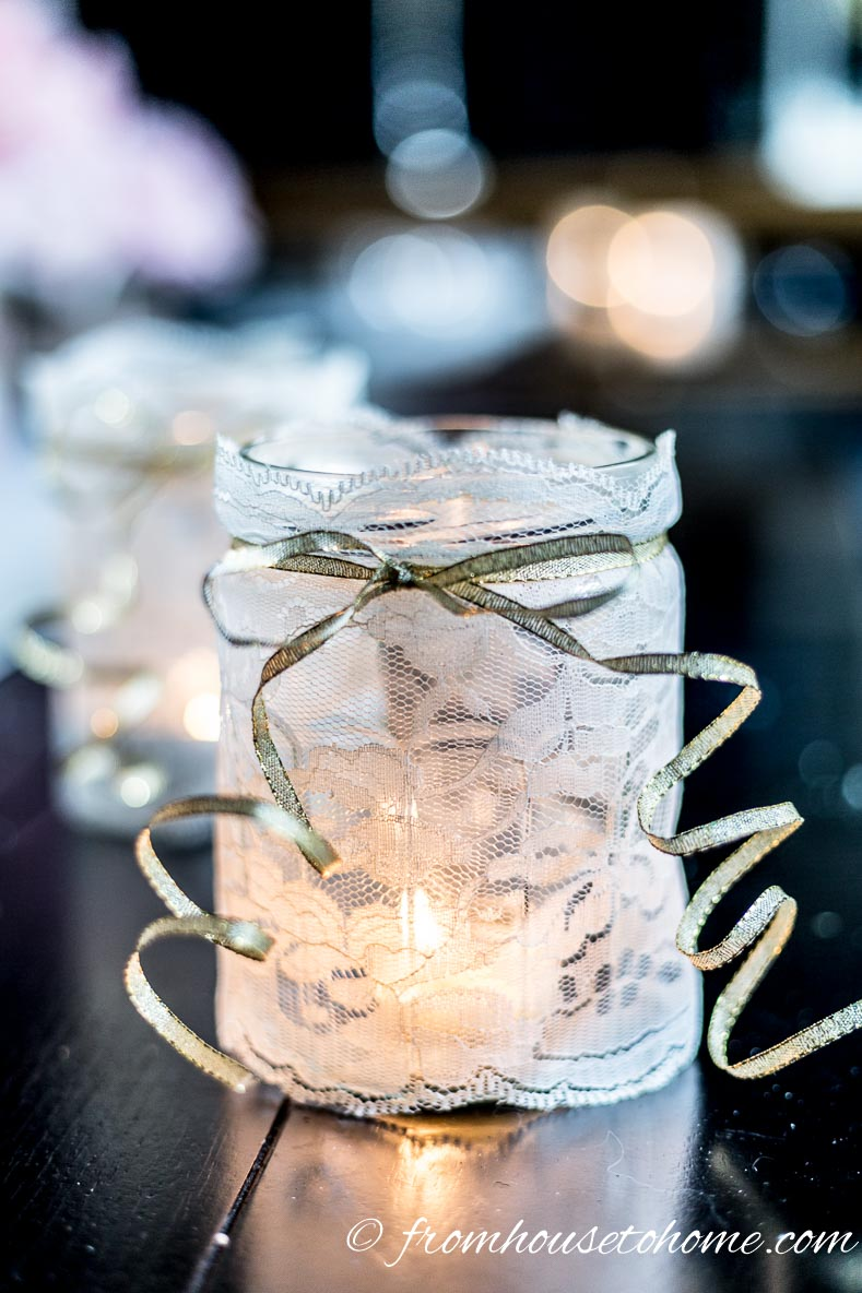 Mason jar wrapped in white lace used as a candleholder