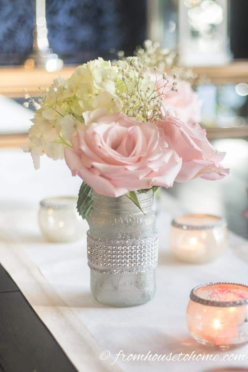 Floral arrangement made from pink roses, white hydrangeas and white baby's breath in a DIY mason jar vase