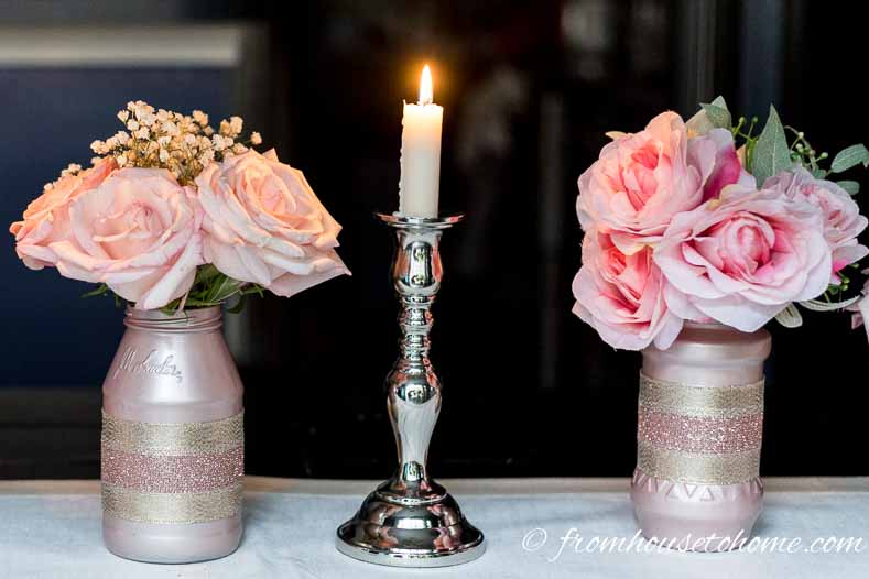 DIY rose gold centerpieces made from glass jars painted pink and filled with pink roses