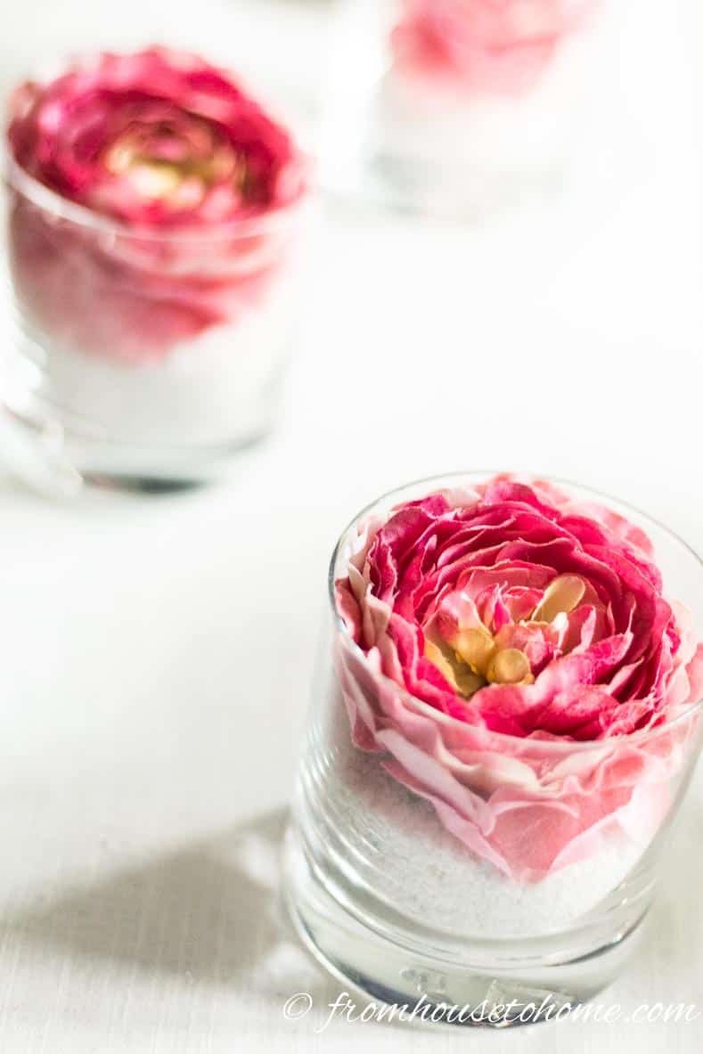 A simple but elegant DIY pink flower centerpiece made with pink floral napkin rings in a glass with white sand