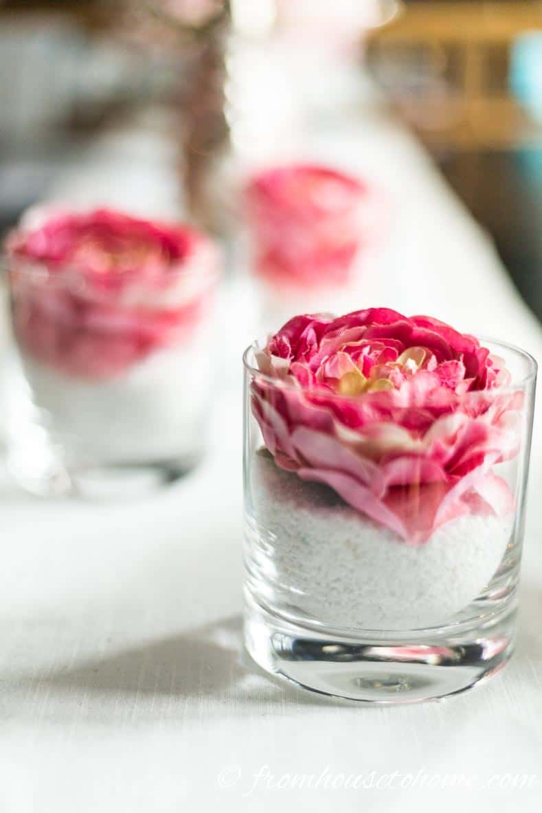 A pink floral arrangement made from a whiskey glass, white sand and a pink floral napkin ring