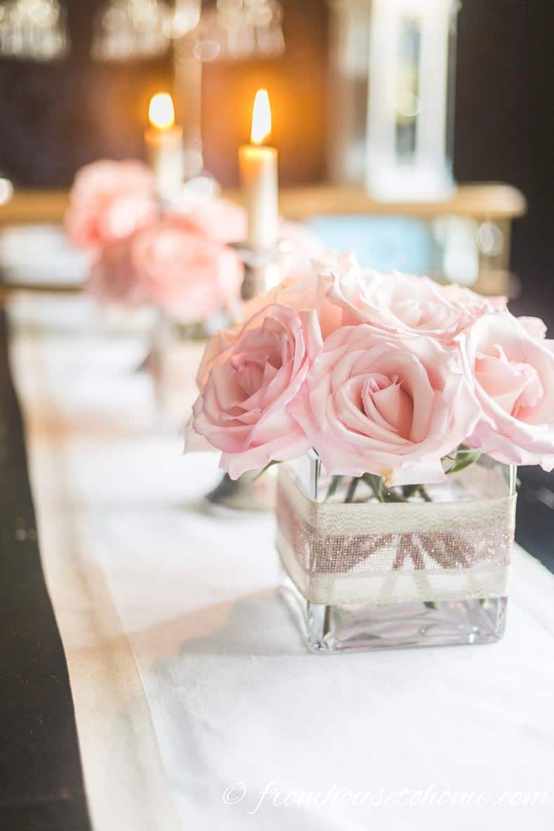 Simple but elegant pink floral centerpiece made with pink roses in square vases repeated down the length of the table