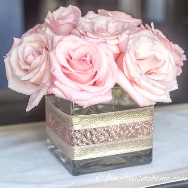 A simple but elegant DIY flower centerpiece made with pink roses in a square vase