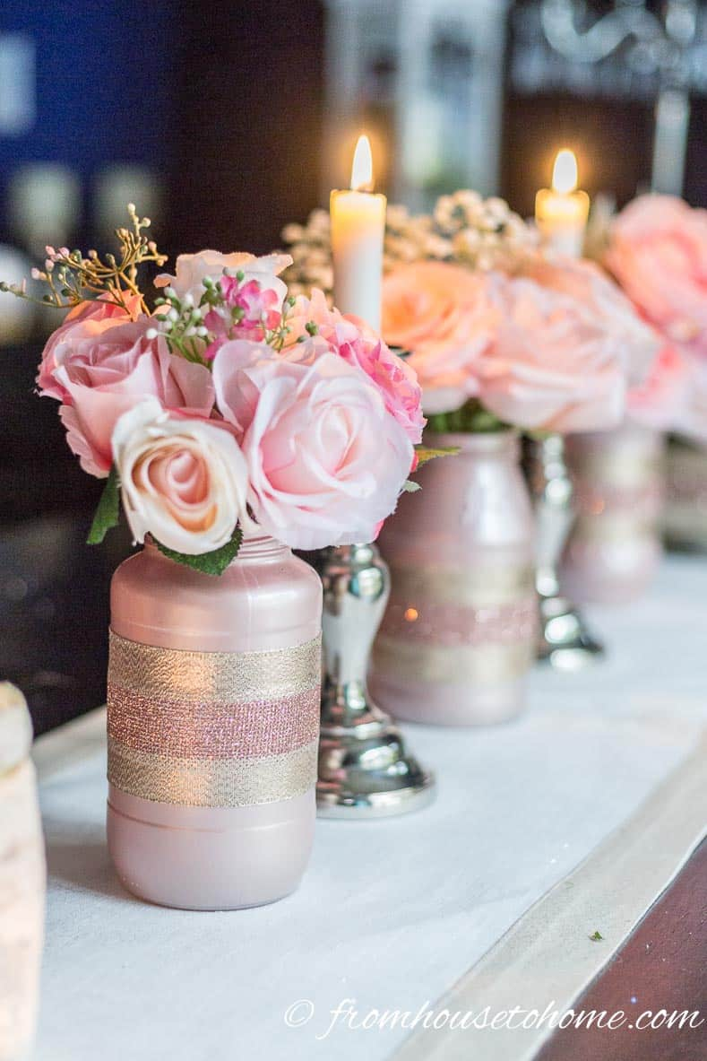 A rose gold centerpiece made with roses and baby's breath in DIY rose gold glass jar vases