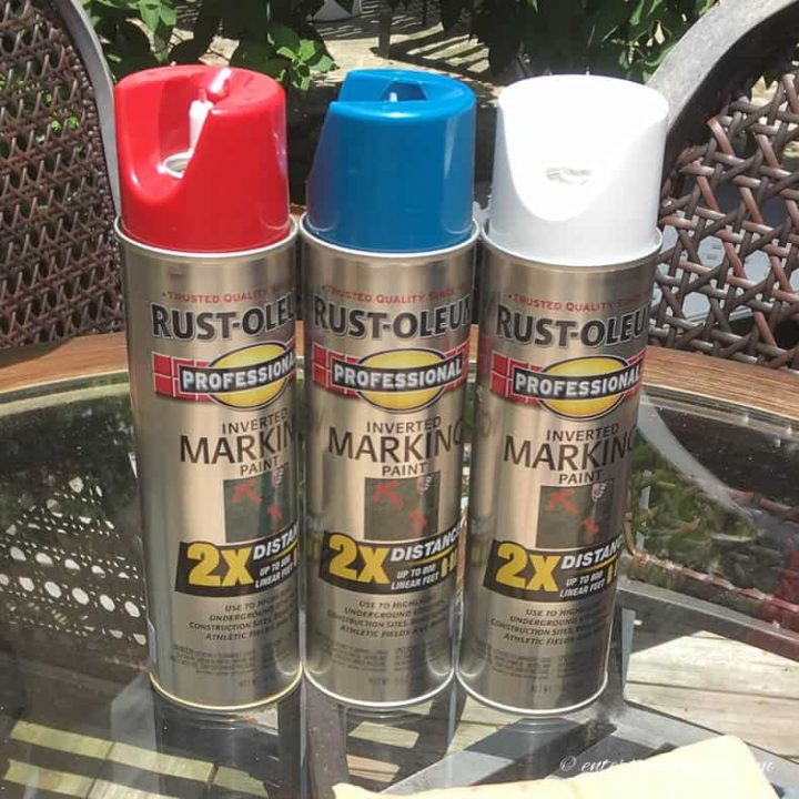 Red, white and blue marking spray paint cans used to make diy patriotic lawn decorations