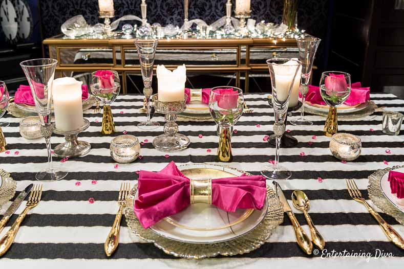 kate spade party decor place setting with white and gold plates, gold cutlery and pink napkins