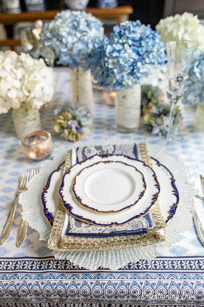 Blue, white and gold napkins on a blue and white place setting