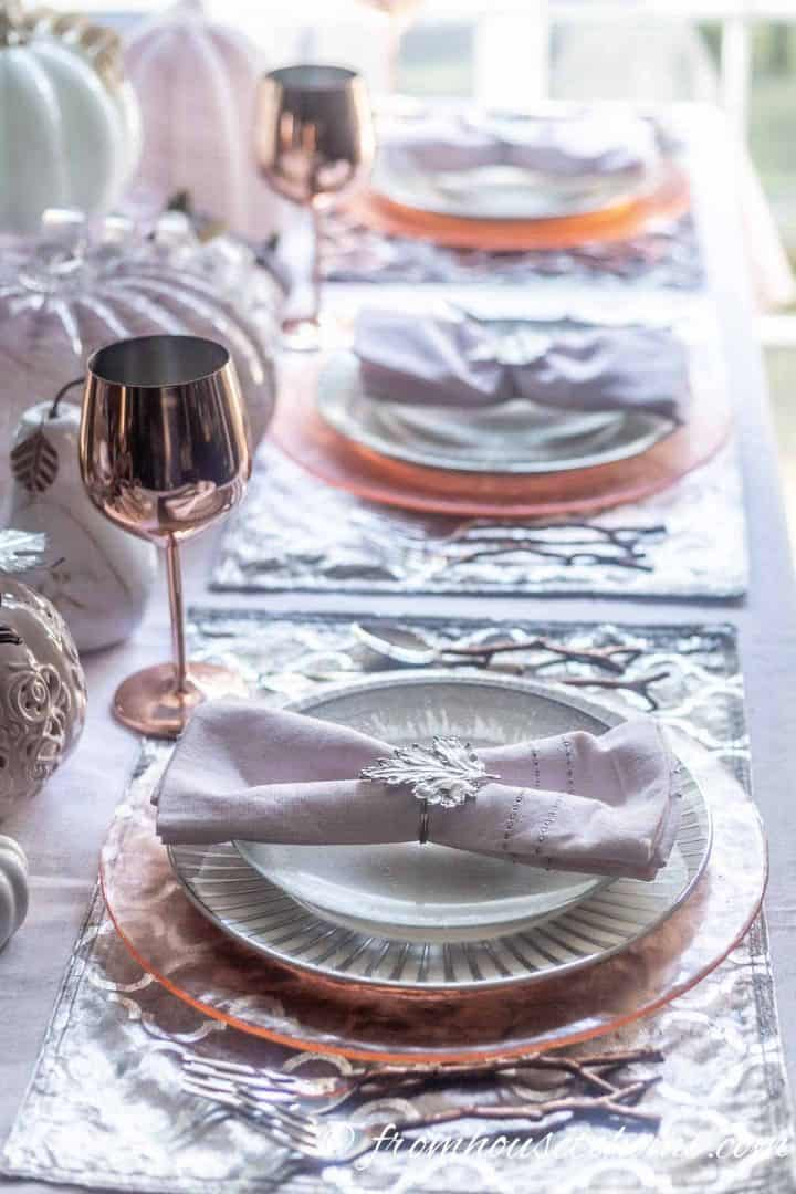 Pink, silver and copper place settings with pink pumpkin centerpiece