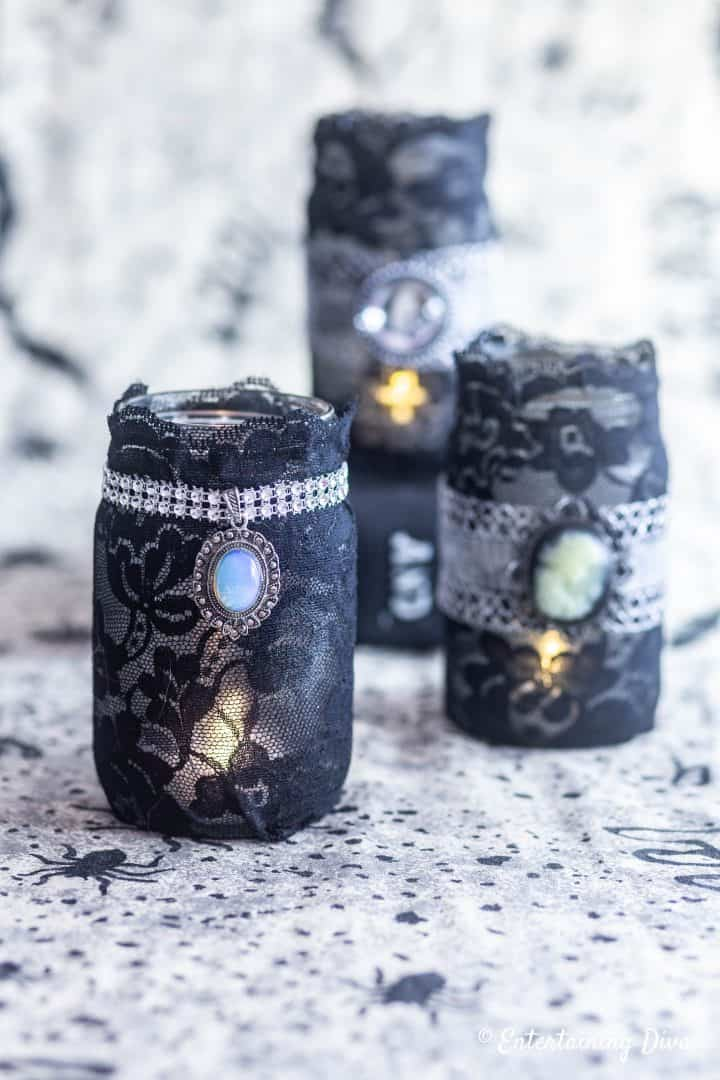 DIY Halloween candle holders made with mason jars, black lace and necklace pendants