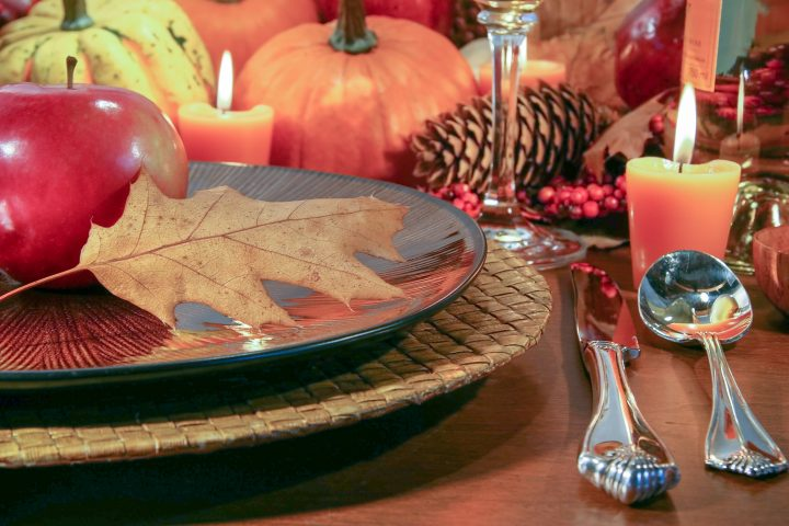 Thanksgiving table with pumpkins, pine cones and apples used as fall decor