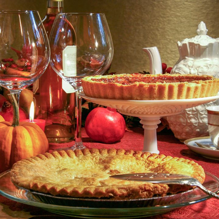Thanksgiving pies on a table with wine glasses