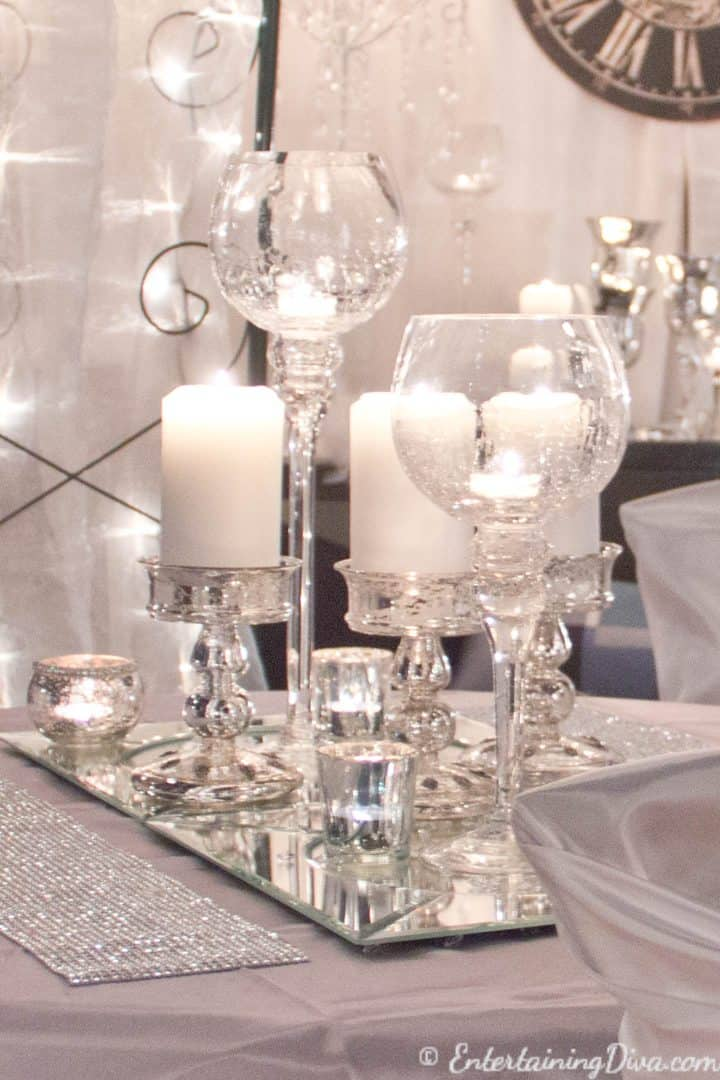 White candles on mirror chargers as a last minute New Year's Eve Party decoration on a table