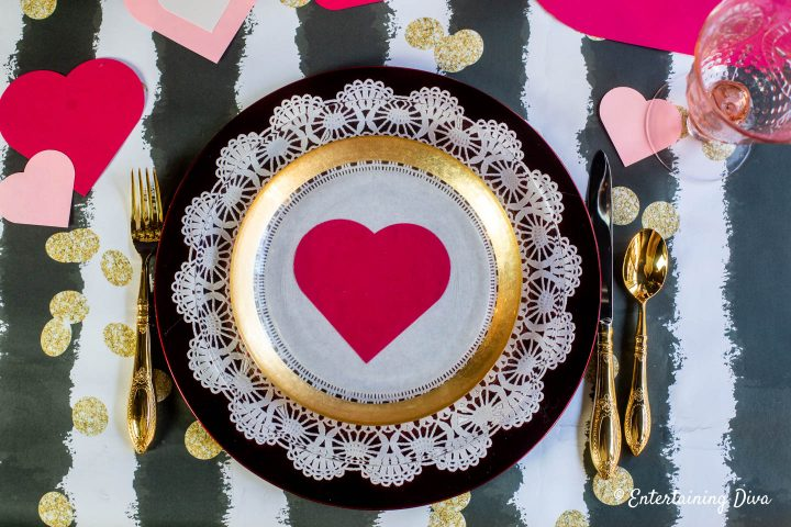 Valentine day table setting with white paper doily on a red charger plate and gold cutlery